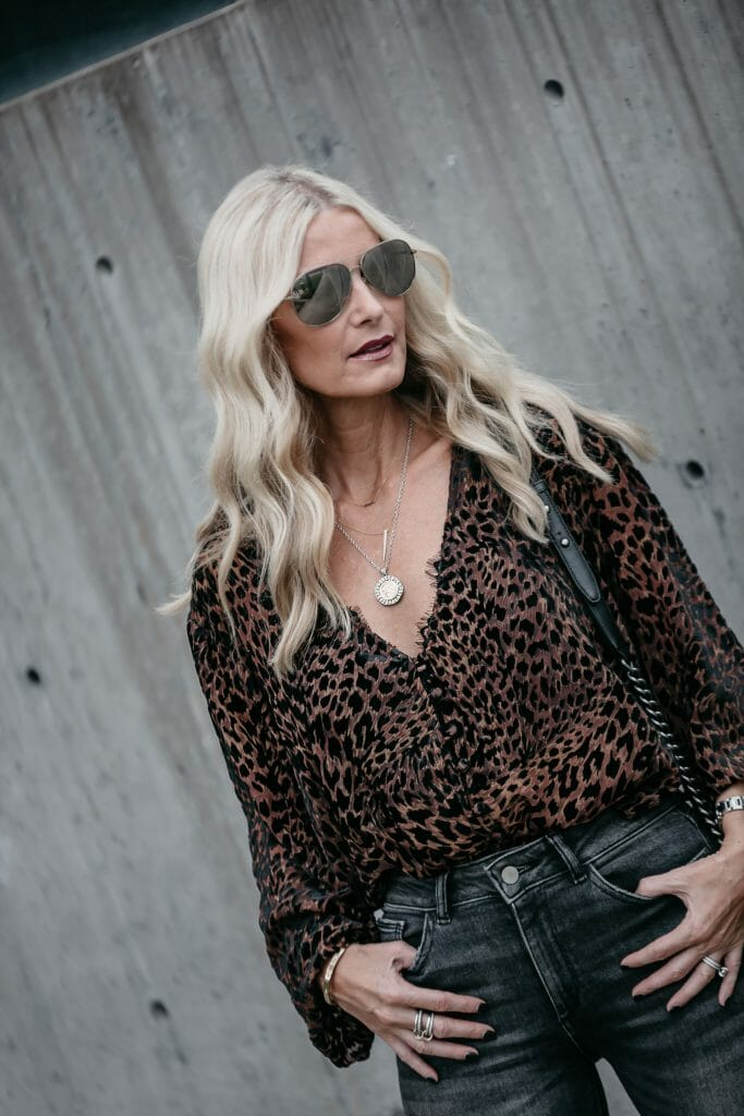 Dallas blonde woman wearing a leopard top and gray skinny jeans