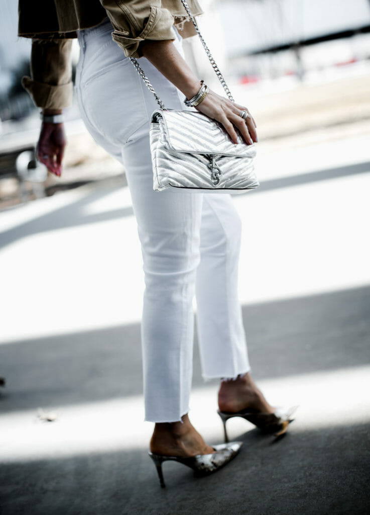 White jeans, Rebecca Minkoff silver handbag, and snake print heels