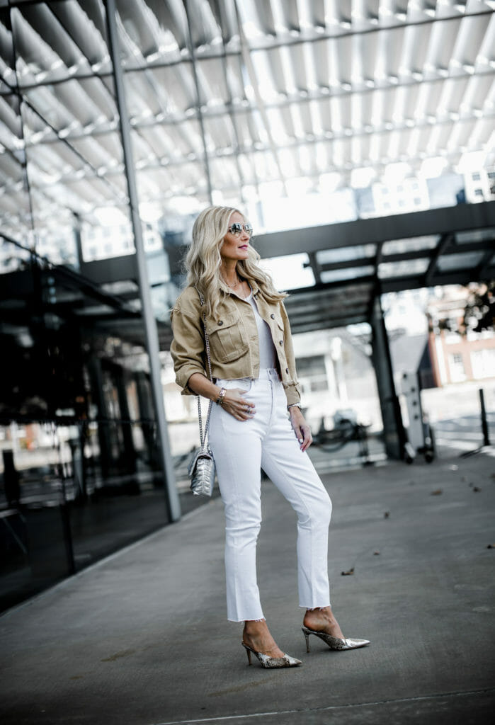 Dallas style influencer wearing Agolde white jeans and snake print heels