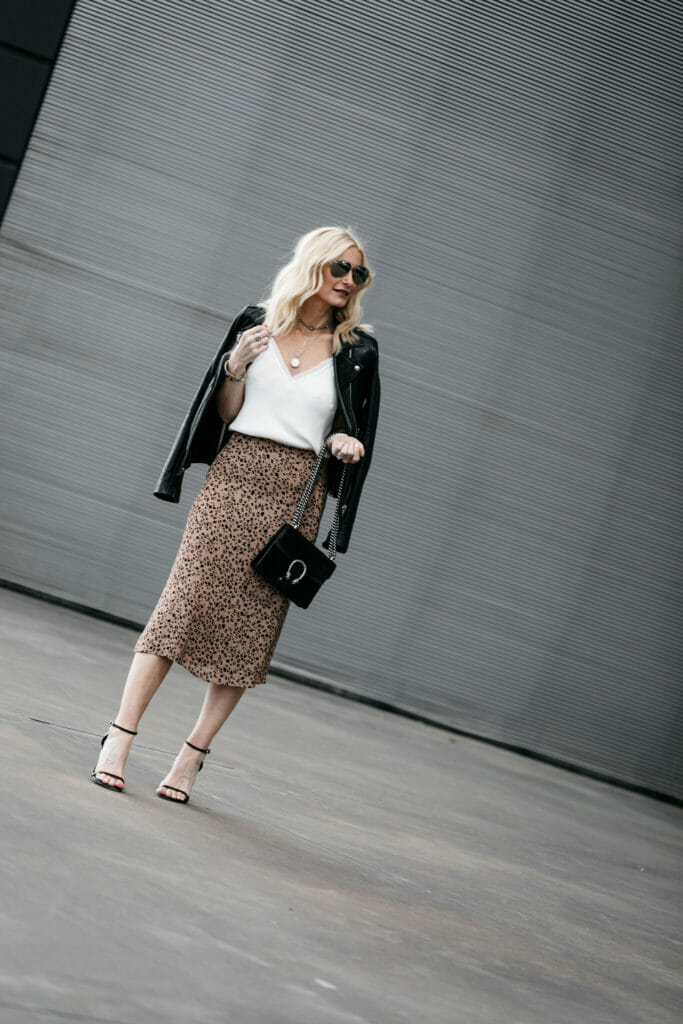 Dallas fashion blogger wearing a leather jacket, midi skirt, and black ankle strap heels