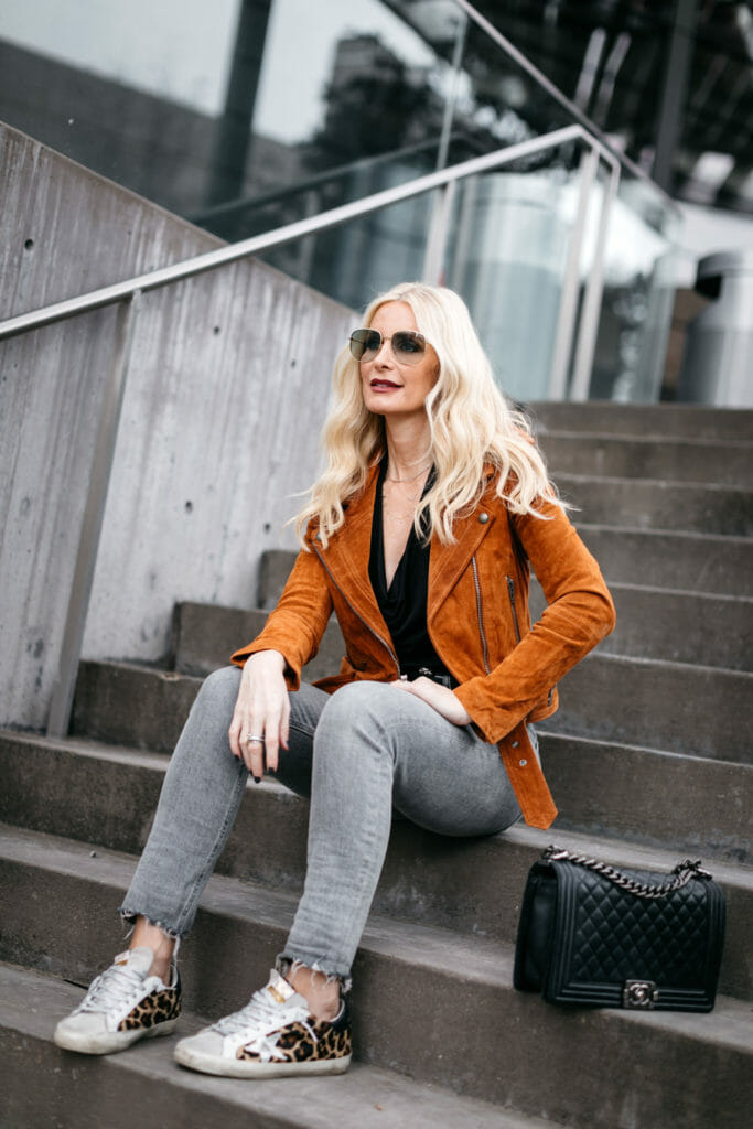 Dallas style blogger wearing a moto jacket and gray jeans