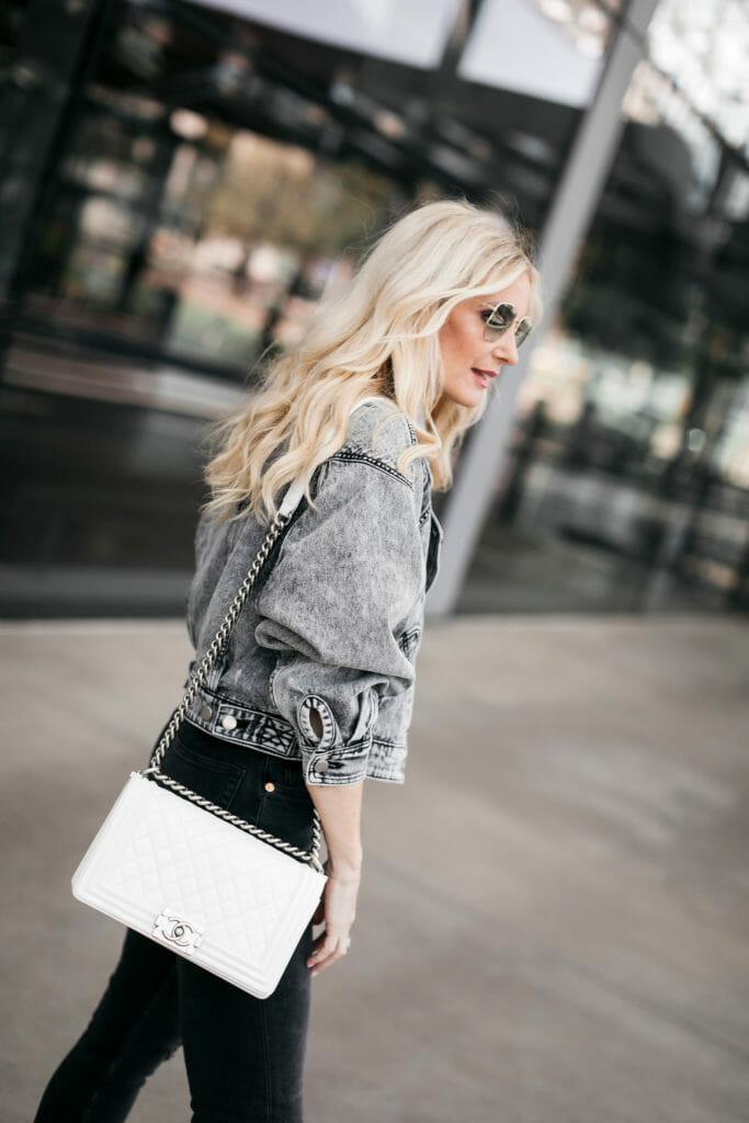 Style blogger wearing a grey denim jacket and a white handbag