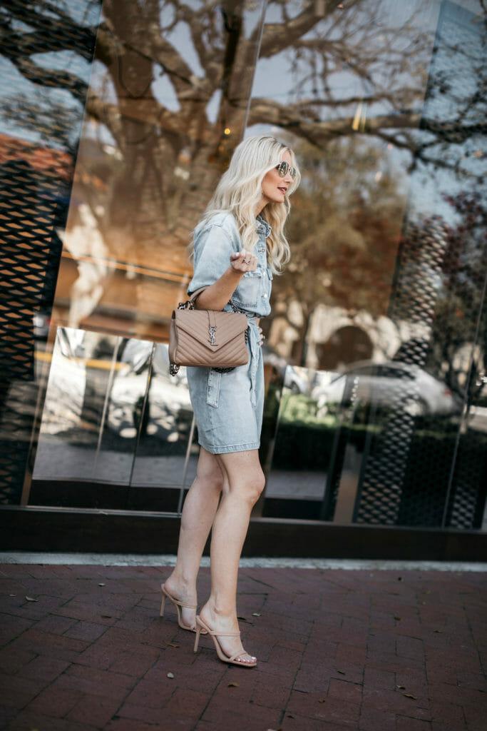 Fashion blogger wearing a designer handbag and a denim dress