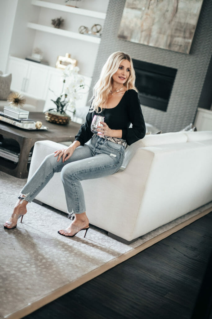 Dallas blogger wearing light wash denim and black and clear heels