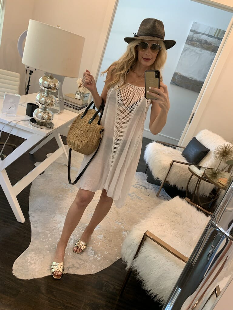 Fashion blogger wearing a white mesh swimsuit cover-up with gold sandals