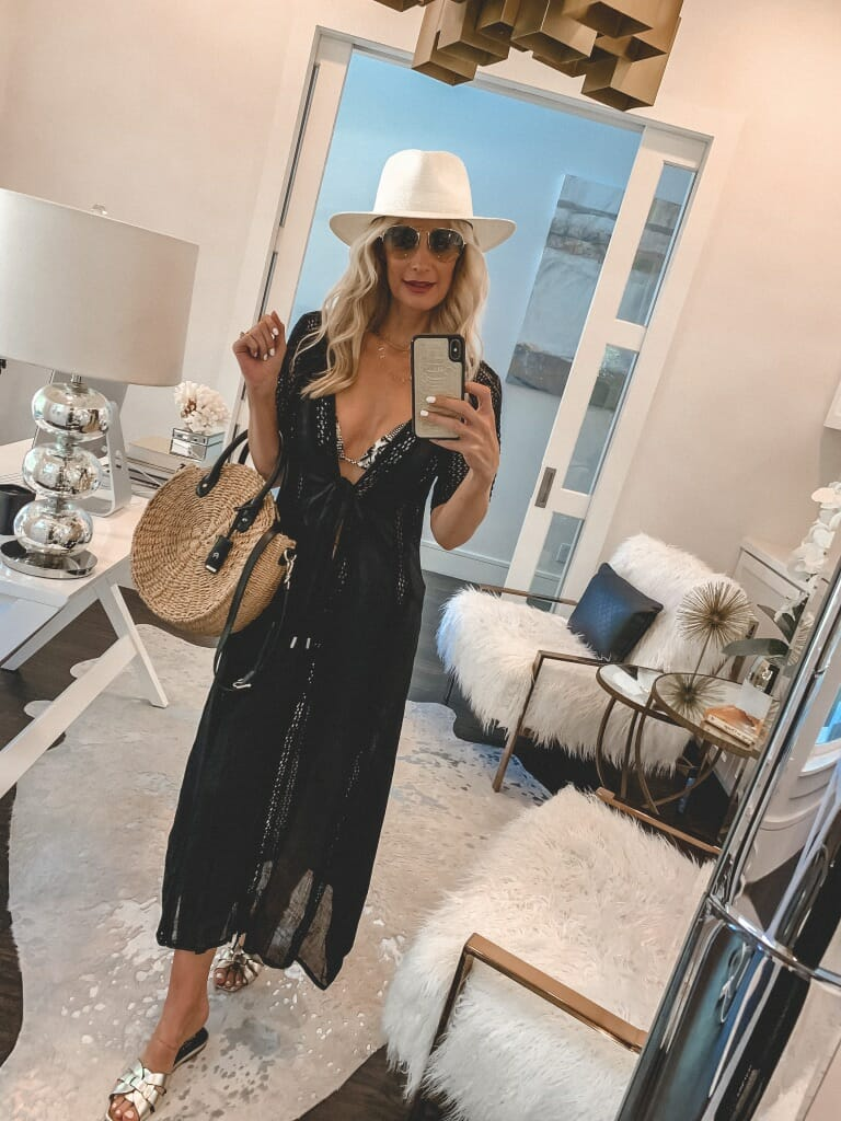 Style blogger wearing a black swimsuit cover-up and a summer hat