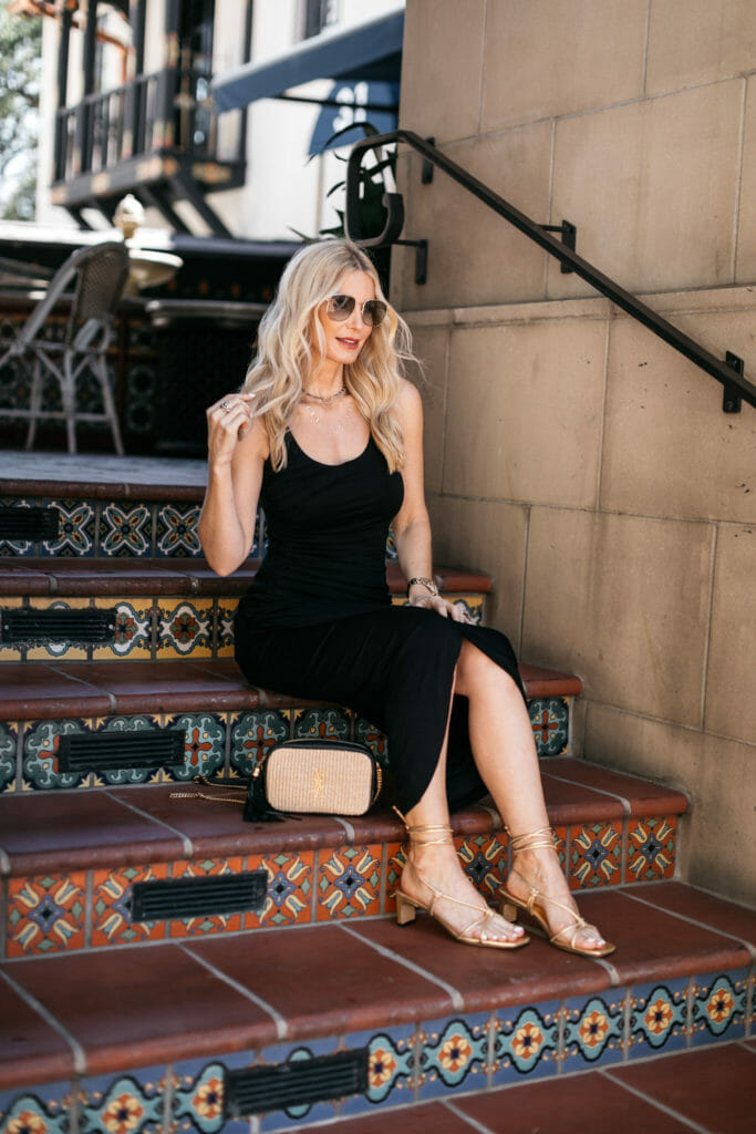 Dallas fashion blogger wearing a black dress and gold sandals