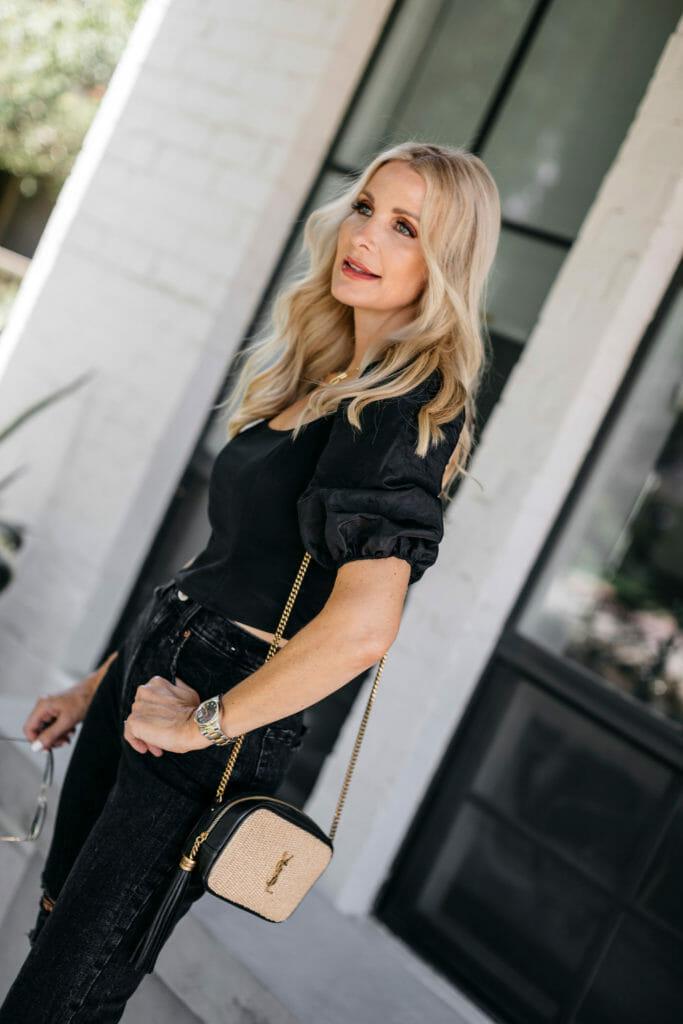 Fashion blogger wearing a black top with black denim and a YSL handbag