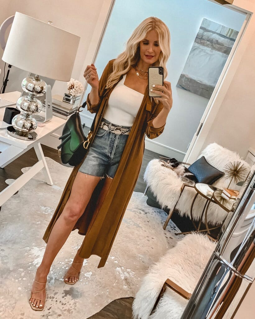 Style influencer wearing a long kimono and denim shorts
