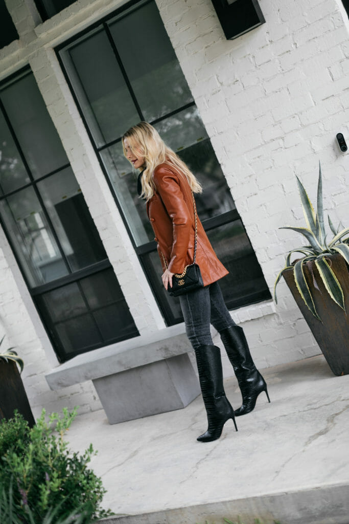 Dallas blogger wearing a vegan leather blazer and knee-high boots
