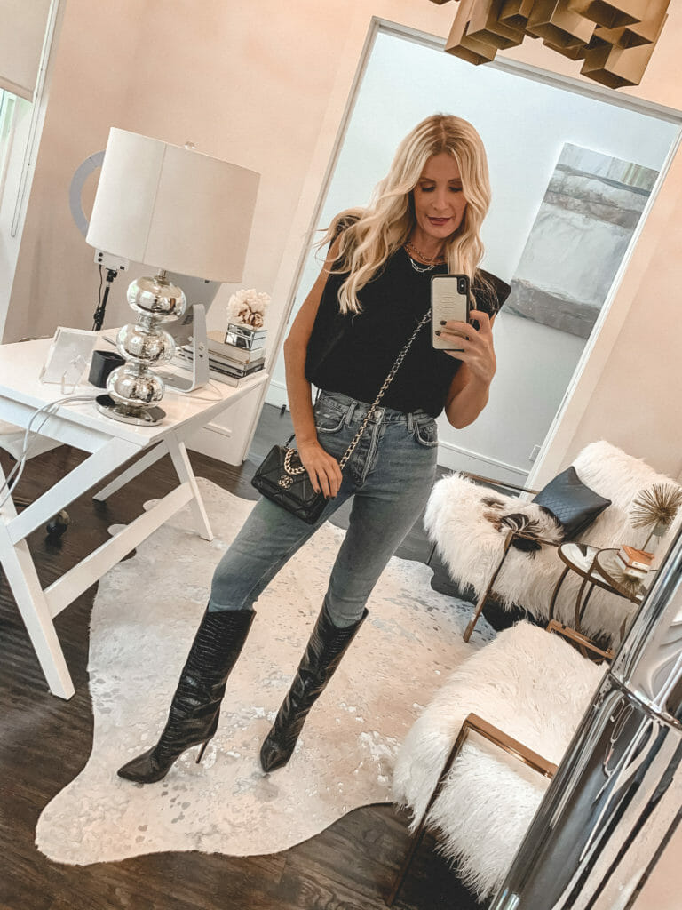 Style blogger wearing a black top with shoulder pads and tall boots
