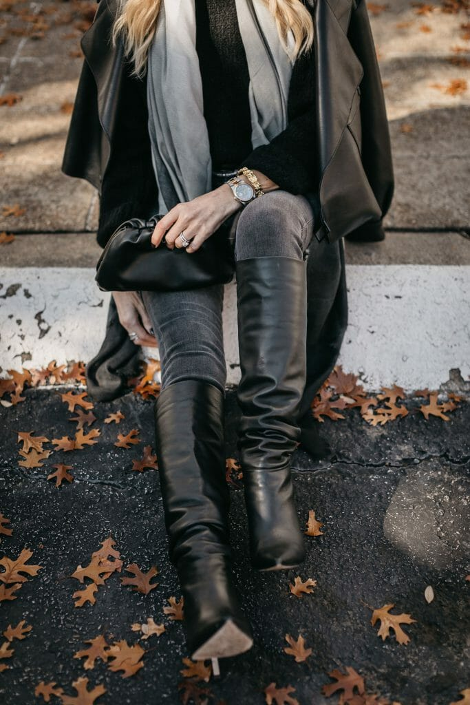 Style influencer wearing black denim and tall black boots for winter