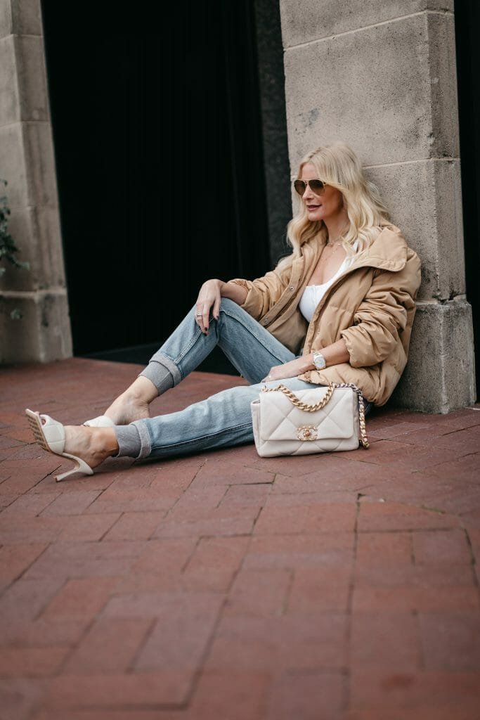 Style blogger wearing a camel puffer jacket and denim joggers