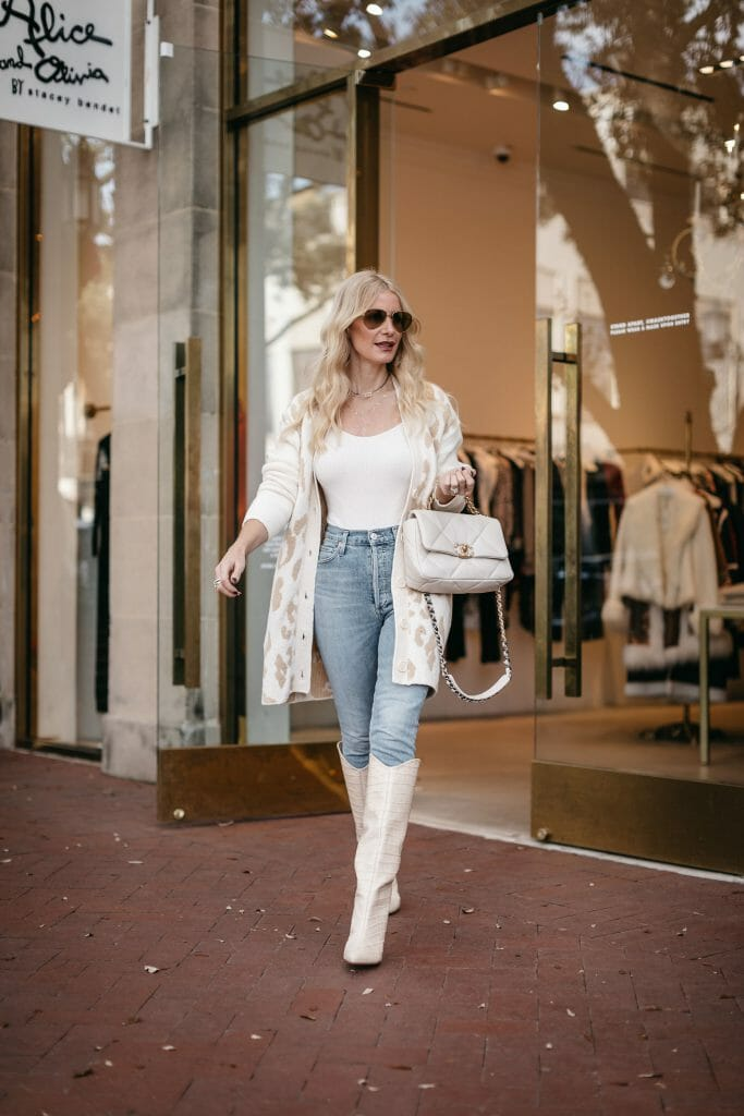 Style blogger wearing a white and camel leopard cardigan and a white bodysuit with white knee high boots