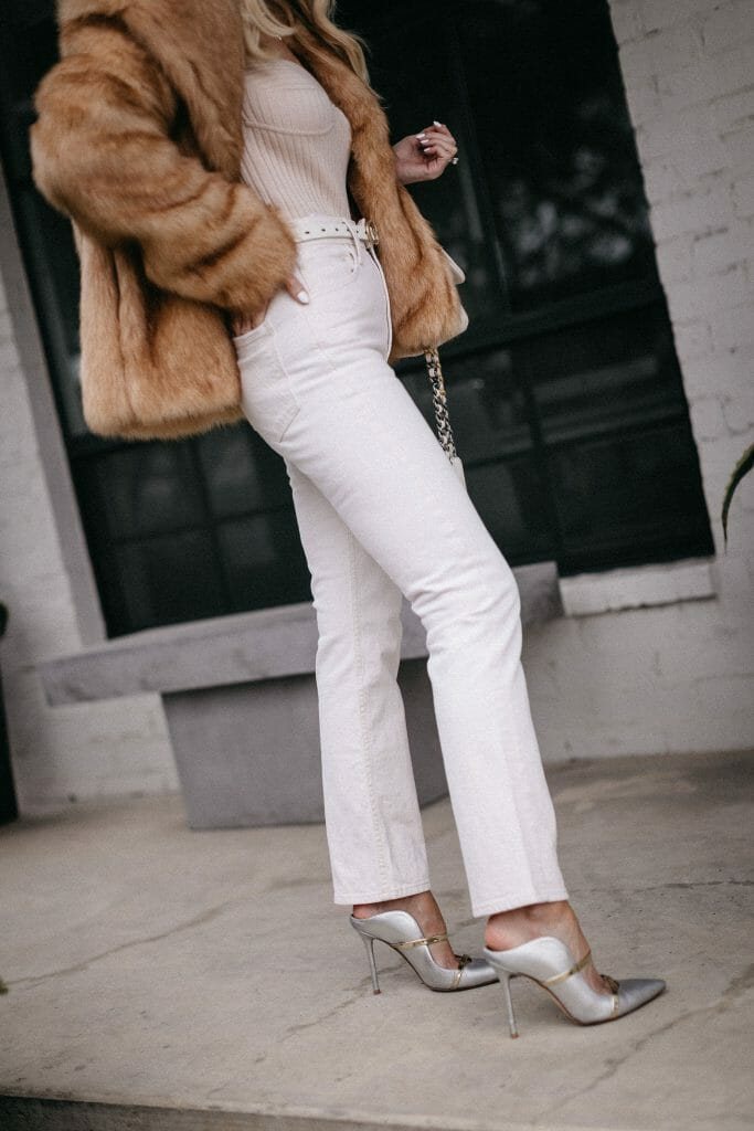 Dallas style blogger wearing white denim and a white belt with a faux fur jacket for winter