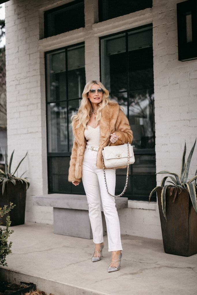 Dallas style blogger wearing a faux fur jacket and white denim