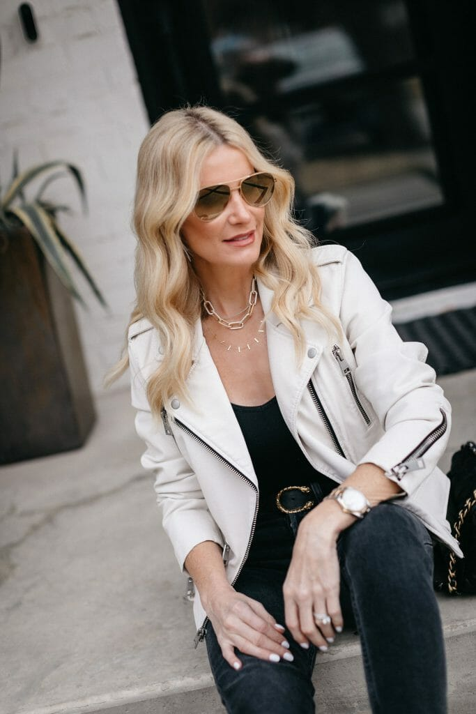 Dallas fashion blogger wearing a black bodysuit and a white faux leather jacket