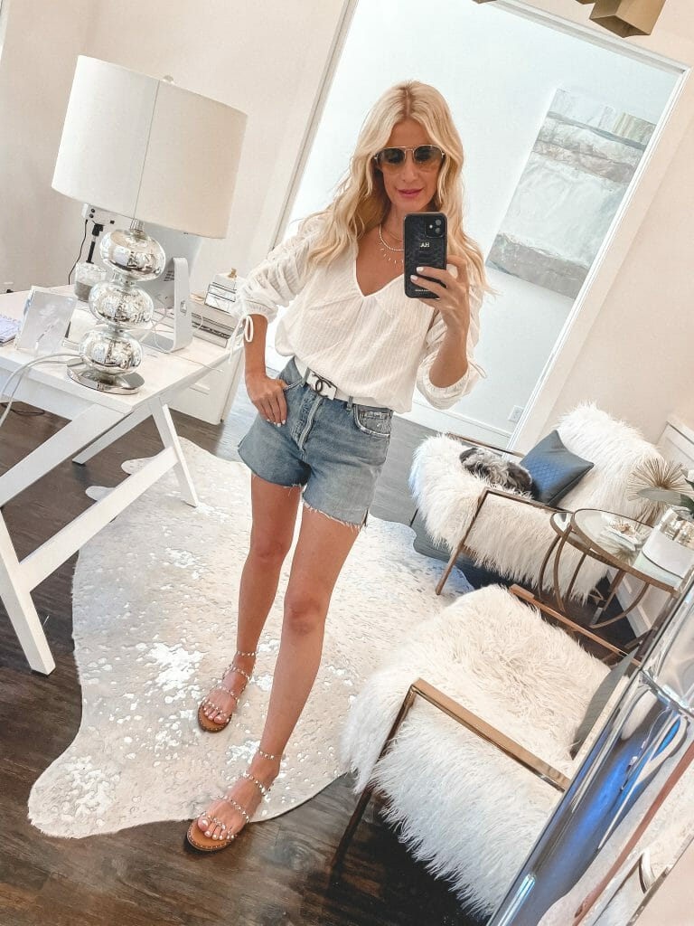 Style blogger wearing a white ruched shirt and denim shorts