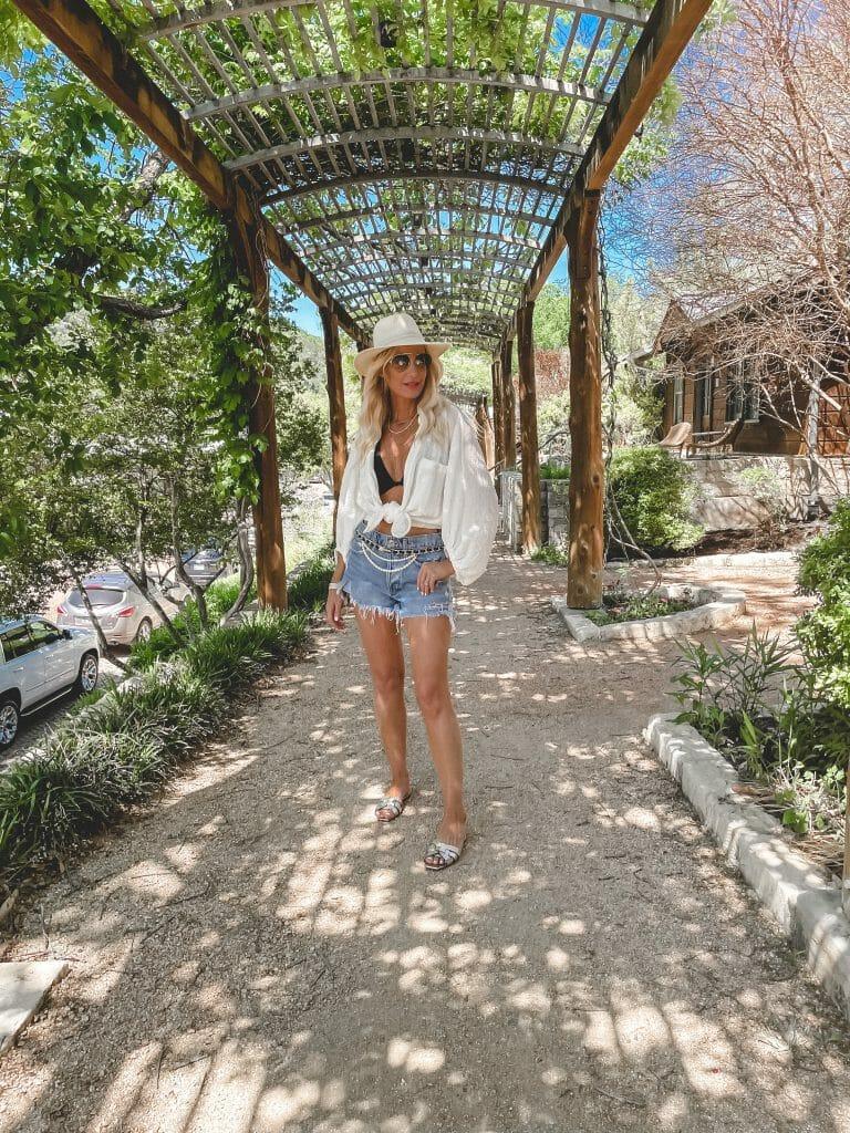 Dallas fashion blogger wearing a white button down shirt and a black bikini top with denim shorts