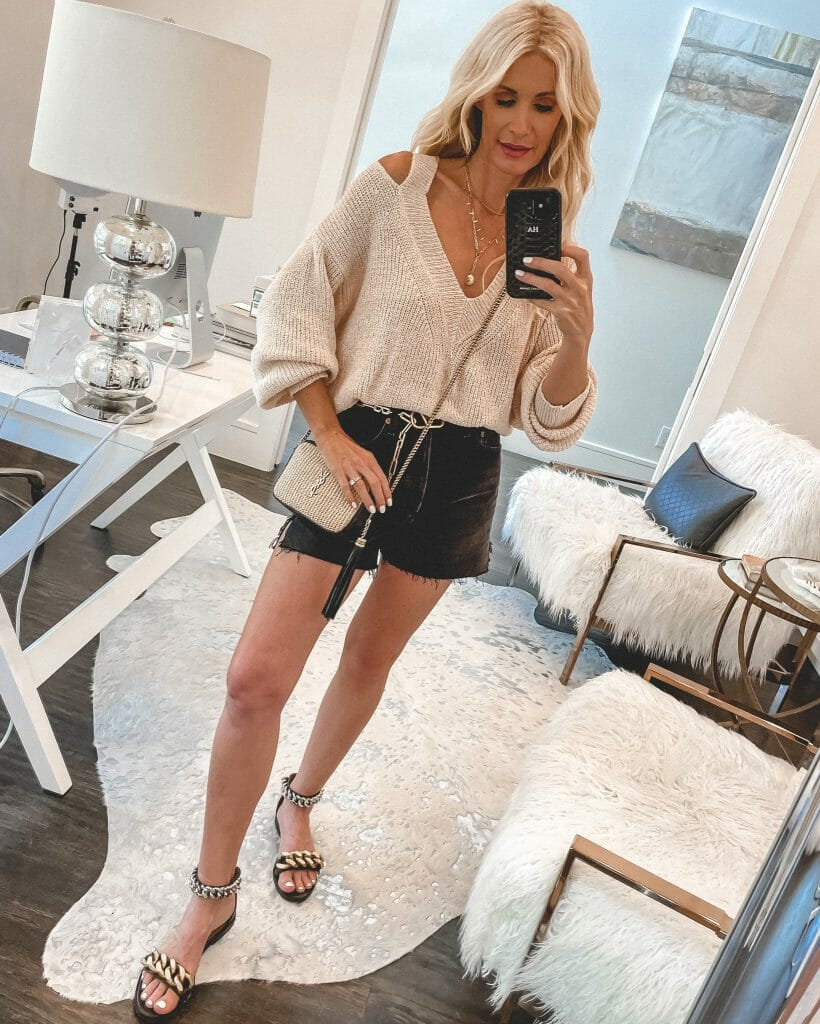 Dallas fashion blogger wearing a cream cut out sweater and black denim shorts