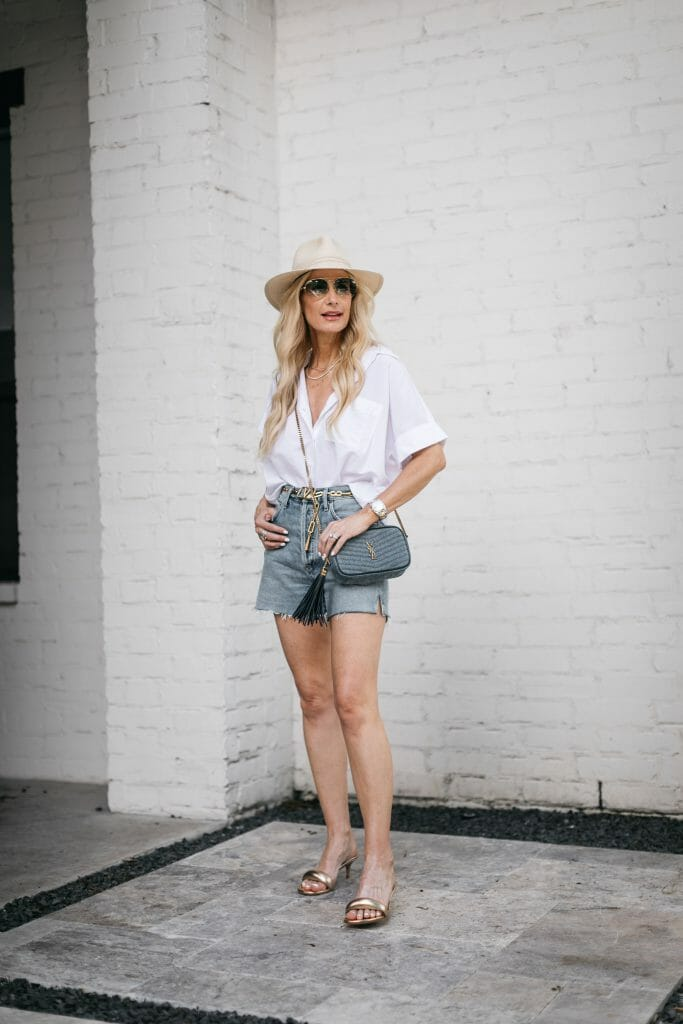 Dallas style blogger wearing a straw summer hat and agolde denim shorts