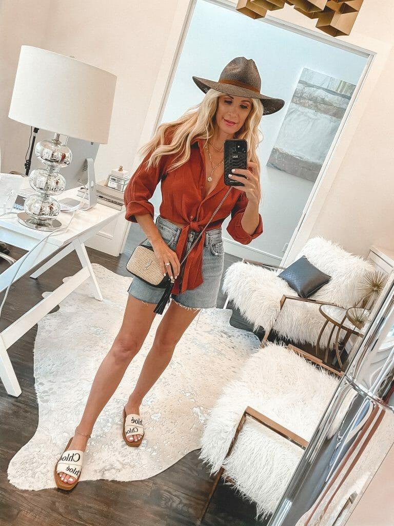 Dallas blogger wearing an orange button down top and Agolde denim shorts