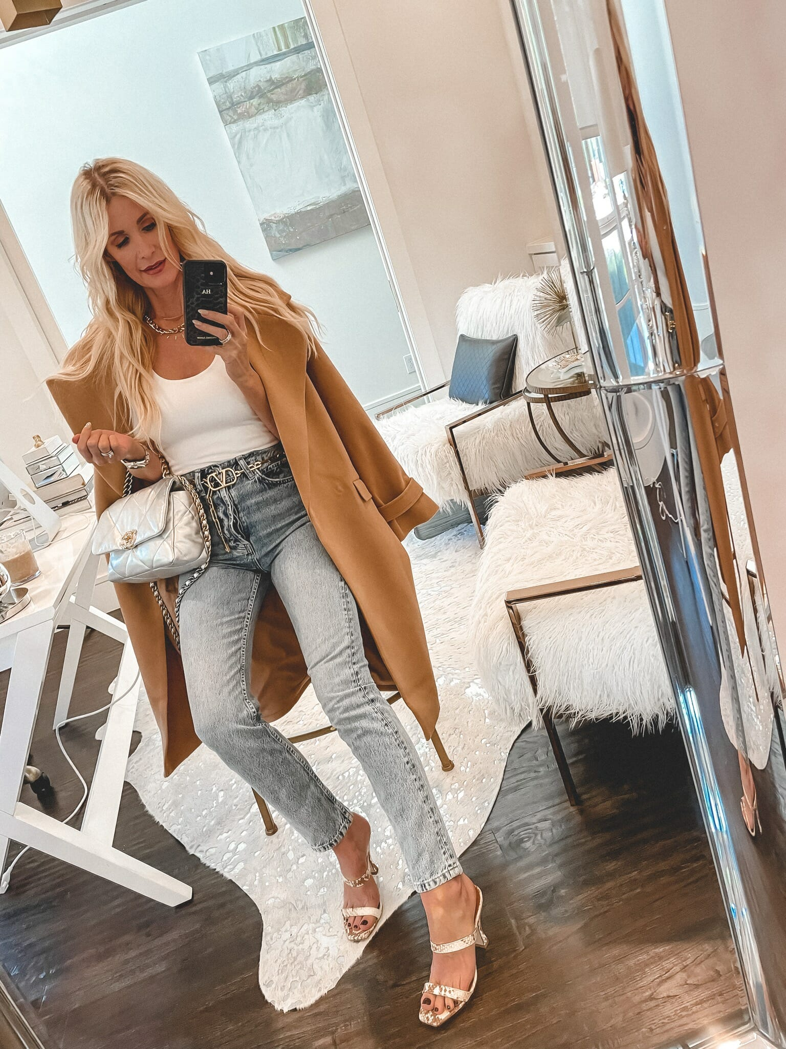 Dallas style blogger wearing a camel coat and a white bodysuit